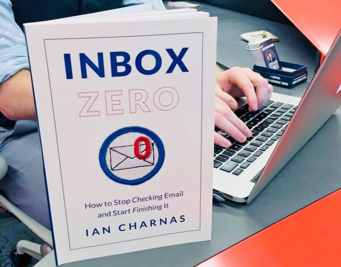 Inbox Zero book on desk next to man with laptop