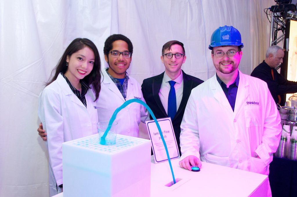 Design team in front of Laser Punch exhibit mid-pour